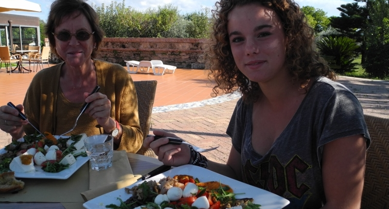 Woman visitor and young girl in front of two big plates with mozzarella cheese and fresh vegetables outdoors in the mozzarella chees farm terrace