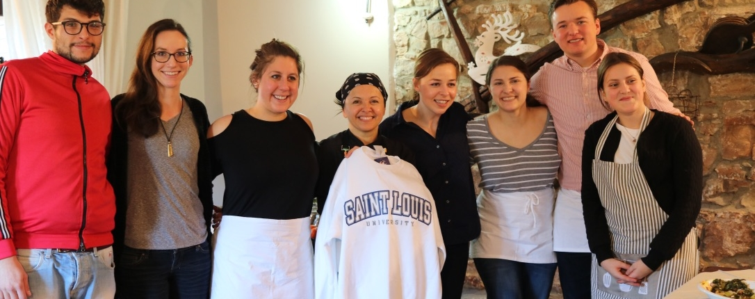 Ogliastro cilento Group picture St.Louis University students with Donatella showing her St.Louis university sweater in the farm dining room