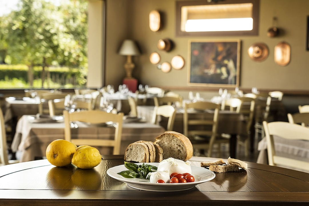 Paestum Vannulo Organic mozzarella cheese on a plate with tomatoes and basil, breads and lemons on the table in the beautiful farm restaurant
